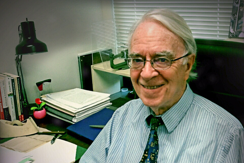 Peter Caws sitting at his desk