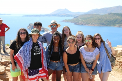10 GW students pose in front of the sea during their Ancient Philosophy Study Abroad trip in Greece. They are smiling and one is